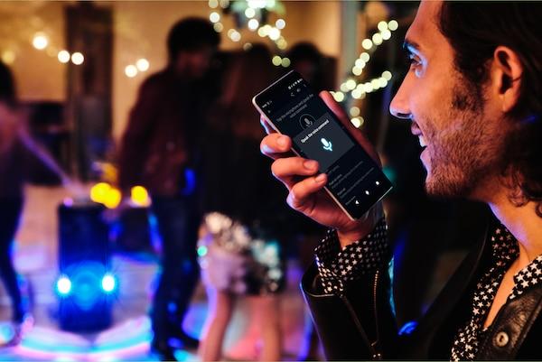Fiestero usando el control por voz a través de la aplicación Fiestable en su smartphone