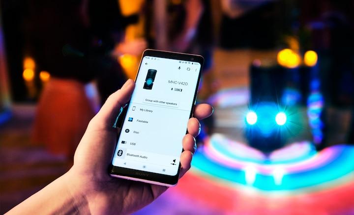 Fiestero usando la aplicación Sony | Music Center en su smartphone